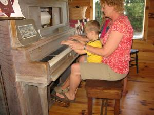 Helping grandson play an old player piano.