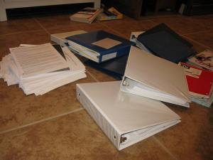Binders and stack of papers still be put in binders.